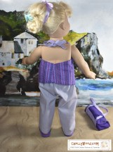 Image shows the Madame Alexander doll wearing the home-made halter top with a ribbon tie at the back of the neck. She's at the beach setting, with her duffel or kit bag nearby (we made that project last week). Her lavender pants coordinate nicely with the purple zig-zag striped halter top. She looks off at the rolling waves in the distance, and the doll's hair is thrown up in a blond messy bun.