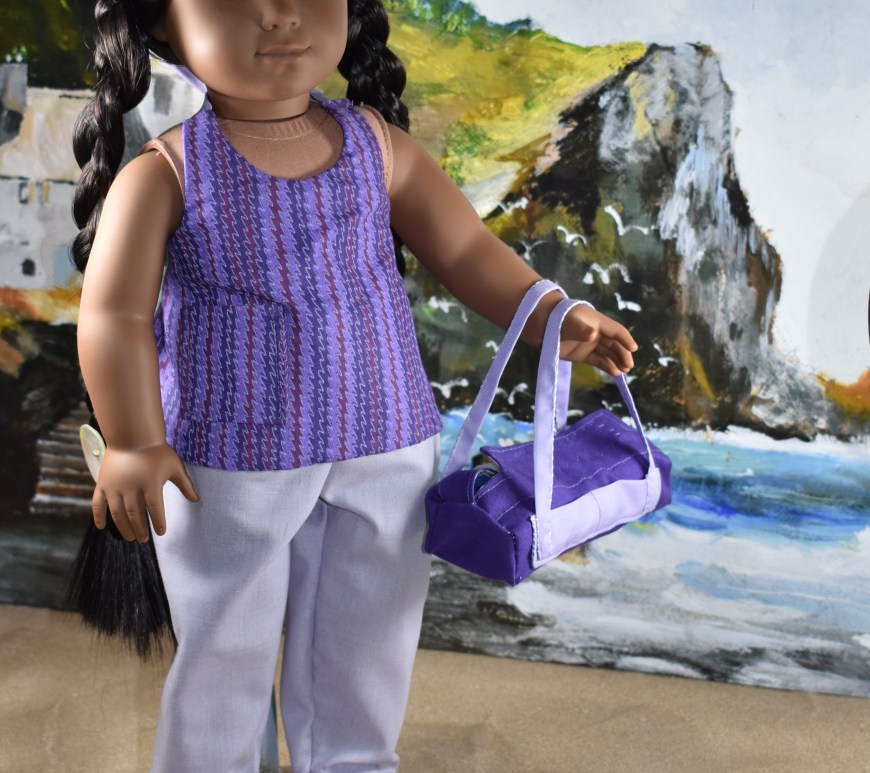 "The image shows a Kaya doll from American Girl wearing a handmade halter top and handmade pants with an elastic waist. She's standing on a beach with a rocky cliff behind her. If you'd like to download and print the free patterns for making the doll's halter top and pants, please go to ChellyWood.com and click on the ""18 inch doll clothes patterns"" link on the home page. Then follow a series of links to a gallery with this pattern displayed."