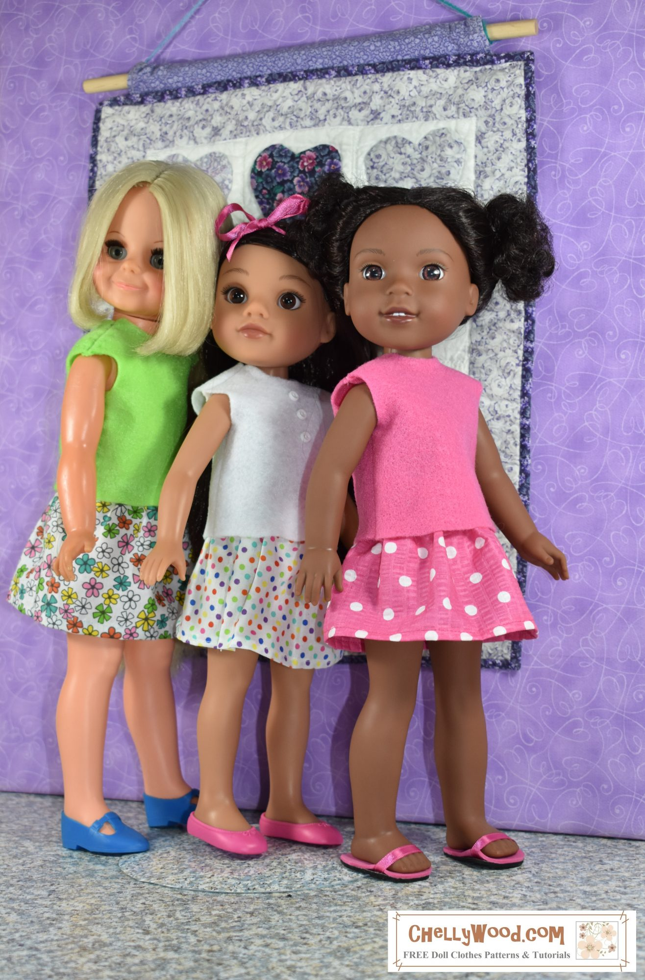 This image shows three dolls lined up in a row (like three friends marching in unison): on the far left is a vintage Velvet doll wearing a green felt shirt with a retro-print floral skirt; in the middle is a Hearts for Hearts Girls Consuelo doll wearing a white felt shirt with a multicolored white skirt; on the right is a Kendall Wellie Wisher doll from American Girl wearing a pink felt top with a matching pink and white polka dot skirt.