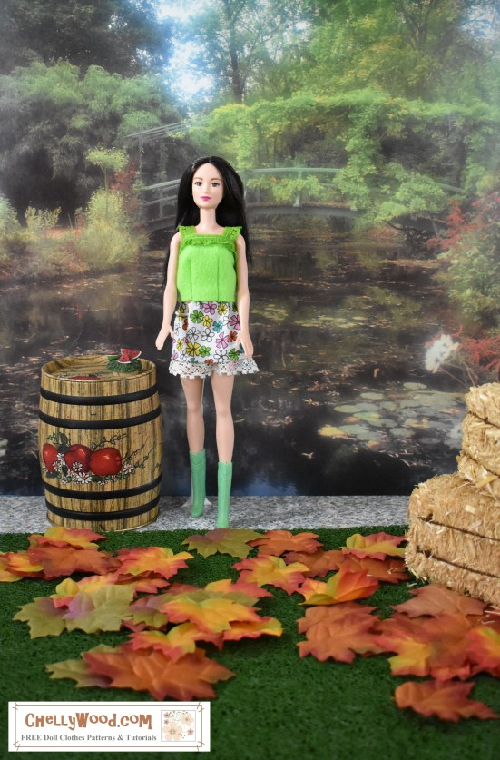 The image shows a fairly traditional Barbie doll wearing go-go boots, a mini skirt, and a summer-style shirt made of felt with lacy ruffled trim. She stands in a diorama with a spring/fall theme. There's a green garden behind the Barbie doll, but the green grass in front of her is sprinkled with autumn leaves. She stands beside a 1/6 scale apple barrel, but on top of the apple barrel is a slice of watermelon, ready for the doll to eat. Nearby two hay bales are stacked one on top of the other. The overlay offers the website where you can find free patterns for making this Barbie shirt and Barbie skirt set: ChellyWood.com (a website that offers free printable sewing patterns for dolls of many shapes and sizes).