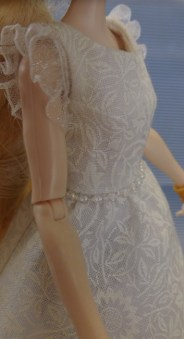 Image shows an Ever After High doll wearing a handmade off-white A-line dress with a beaded waist and lace-ruffle sleeves. The pattern used to make this dress is an alteration of a free pattern found at ChellyWood.com.