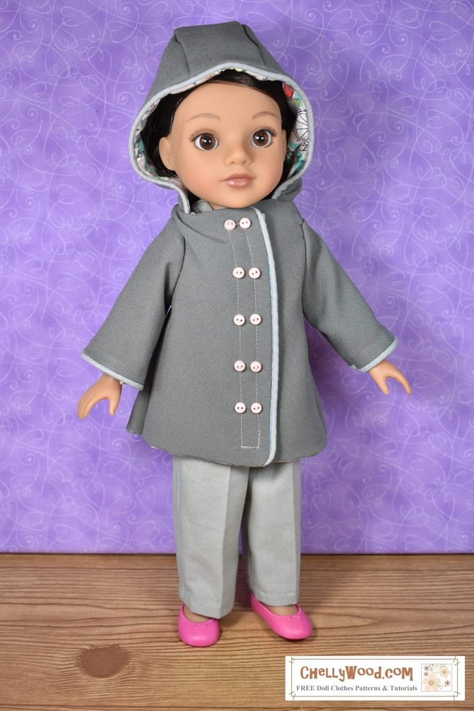 """This image shows a Hearts for Hearts (H4H or Hearts4Hearts) girl (doll) wearing a hand-made raincoat with a hood. The raincoat uses piping along the front placket, the opening for the hood, and the sleeves. The front placket offers a double-breasted looks, although it's actually sealed with Velcro. The topstitching on the front placket has pairs of tiny pink buttons running down the front of the coat. Inside the hood, we see a peek of pink cotton fabric with a London-themed print, which was used to line the coat with cotton lining. This hooded rain coat is made of Polyester, which gives it a plastic-like sheen and the doll's eyes shine brightly out from under the hood of her coat. The watermark says, """"ChellyWood.com"""" and suggests that the website has free printable patterns and tutorials."""