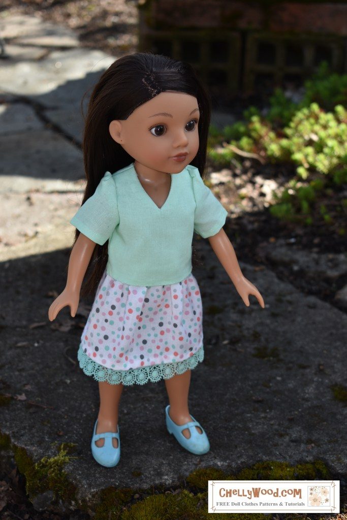 The photograph shows the Consuelo doll from the Hearts for Hearts Girls collection wearing a V-neck blouse with a pretty white cotton skirt that's dotted with random colorful spots and trimmed in a lime green crocheted trim that matches the green of her short-sleeved blouse. She appears to be standing in a tiny garden with bright spots and shadows painting the ground behind her.