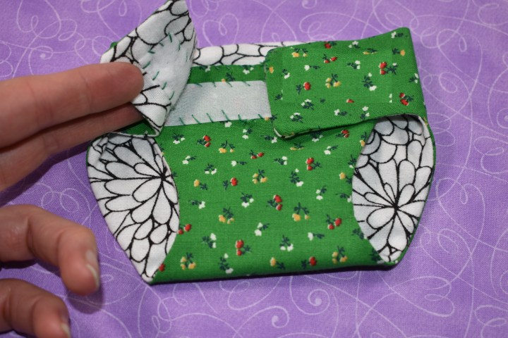 The image shows a doll diaper that uses Velcro to close the diaper flaps.