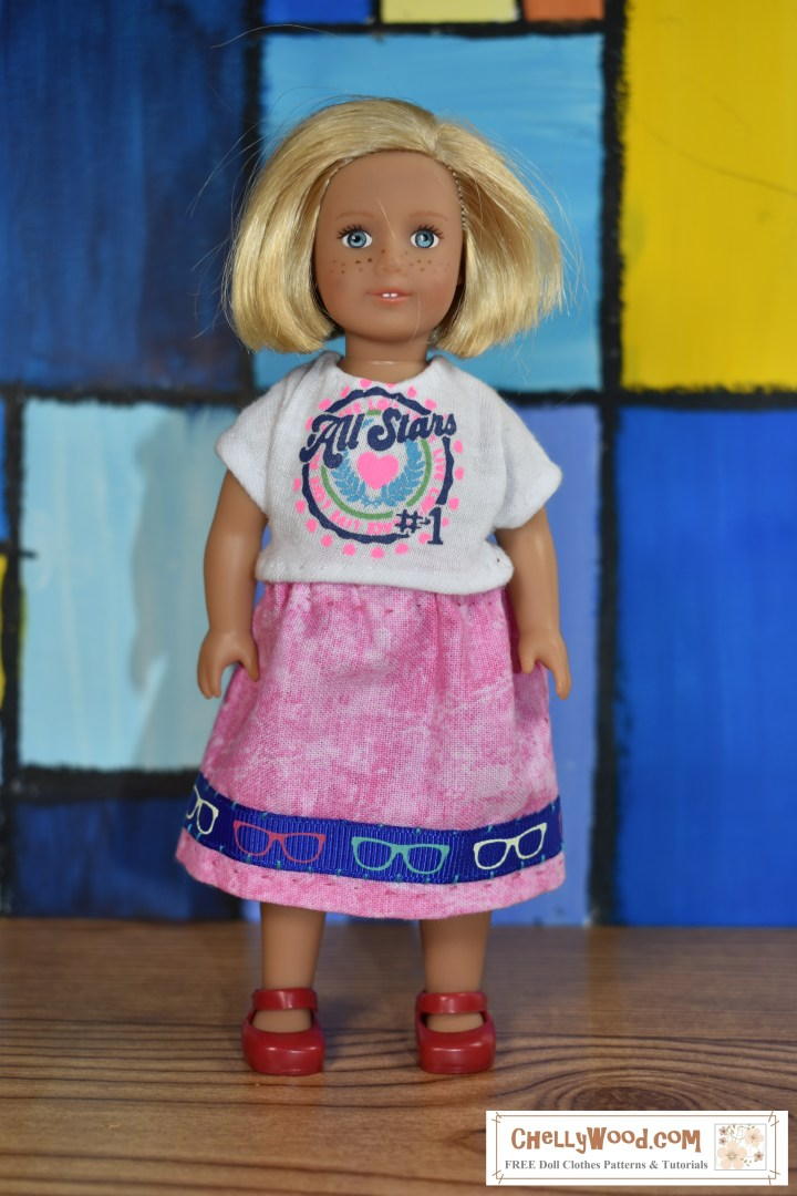 "The image shows the 6"" mini American Girl doll wearing handmade clothes including a skirt trimmed in ""hipster glasses"" ribbon, and a screenprinted T-shirt in matching pinks and blues. The doll stands before a 1960's style blocky wall of stained-glass-style art, almost as if the wall is a mural of colorful rectangles and squares. The blue shades in the wall art makes the hipster-glasses trim on the tie-dyed pink skirt really pop! There's a watermark which offers the name of the website where you can download the free printable pdf pattern for sewing both the tee shirt and the hipster-glasses-skirt: ChellyWood.com (free printable sewing patterns for dolls of many shapes and sizes). This website has lots of free patterns, including the pdf pattern for a 6-inch AG doll wardrobe which includes this skirt pattern and the t-shirt pattern."