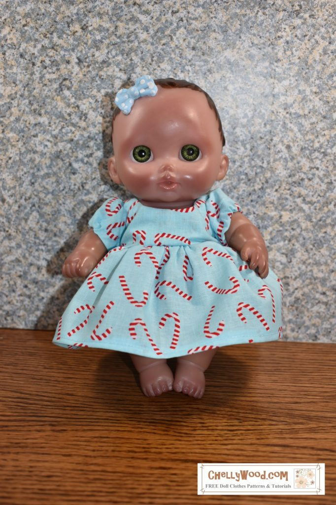 A Lil Cutsies (AKA Lil' cutesie) baby doll from JC Toys is shown modeling a blue dress with sleeves. The cotton dress has a pattern of tiny candy canes dancing across the fabric. The shade of blue in the dress matches the blue of her hair ribbon.