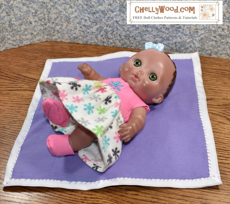 Lying on homemade baby blanket is a Lil Cutesie 8 inch baby doll (AKA Little Cutesie) wearing a handmade doll dress. The dress is sleeveless and it has a pink felt bodice attached to a white cotton flannel skirt that's decorated with tiny snowflakes. She wears pink felt booties to match the dress bodice, and barely visible under her dress is a matching diaper. All of these doll clothes patterns are free at Chelly Wood dot com.