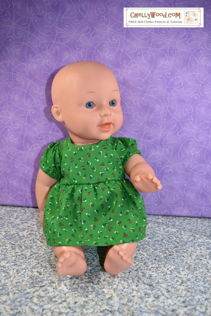 In this photo, we see a 12 inch baby doll with blue eyes and  pink complexion. She wears  green cotton floral dress with puffy short sleeves. The dress has a gathered skirt.