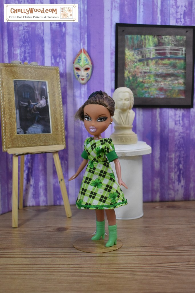 The image shows a Bratz doll wearing a pretty green plaid dress with short puffy sleeves and solid green cuffs. The fabric pattern includes shamrocks among the plaid squares. This Bratz doll seems to be standing in an art museum, which displays a Monet garden-themed painting, a bust of Bach, a sculpted harlequin mask, and a famous painting of Romeo and Juliet in the museum diorama. The watermark reminds you that you can find the free printable sewing patterns and free tutorial videos for making this doll dress at ChellyWood.com