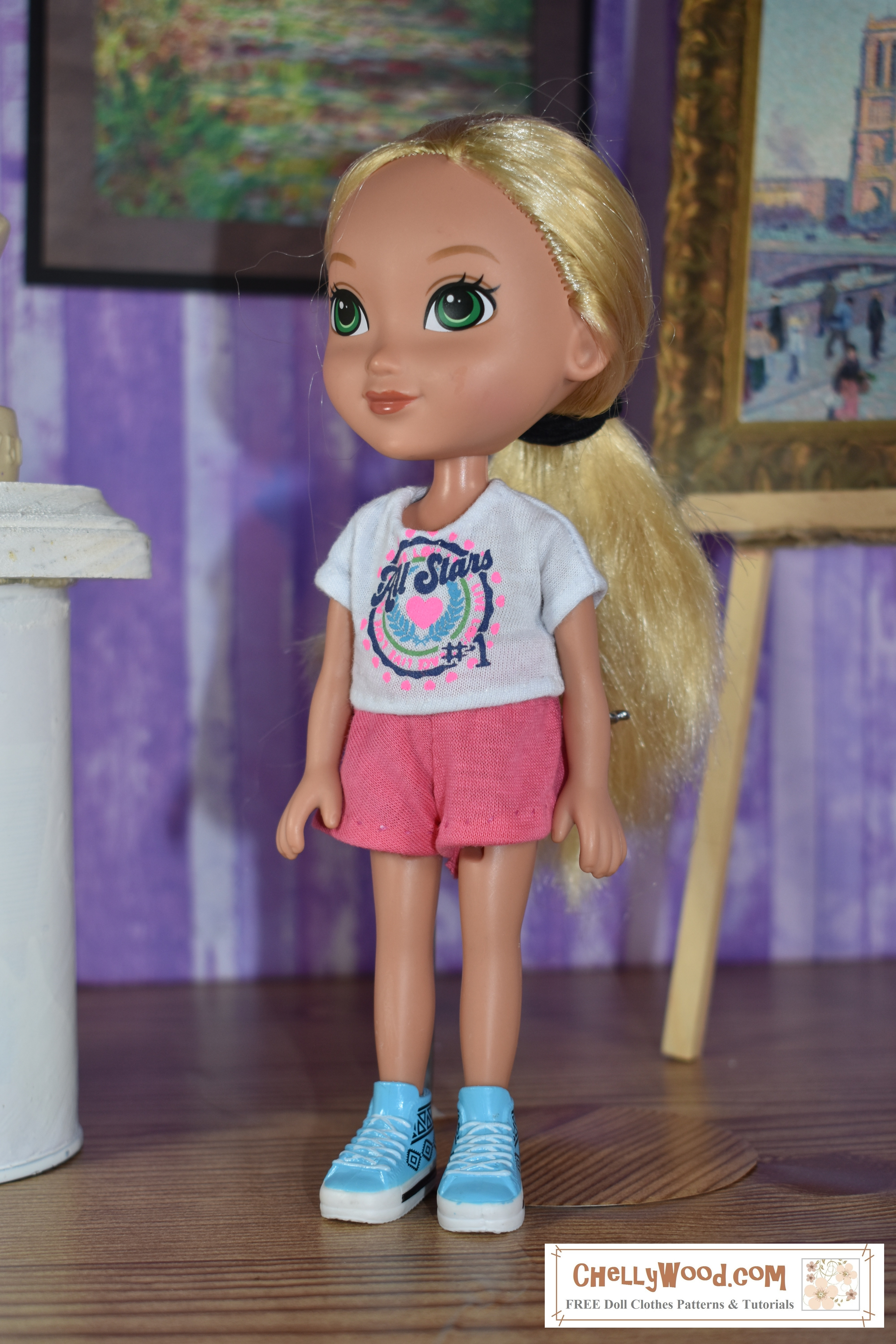This is a photograph of the Dora the Explorer friend doll called Alana, wearing handmade shorts and a graphic tee shirt. She stands among statues and paintings in an art gallery. The tee shirt and shorts she wears are made of jersey fabric.