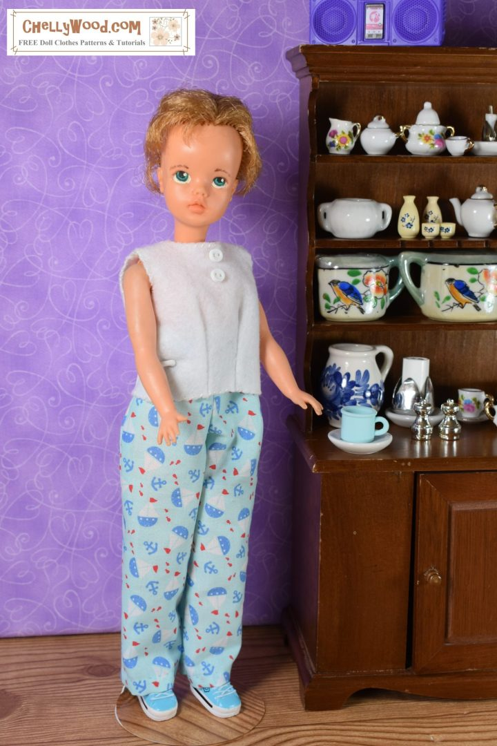 Here we see an Ideal Tammy doll standing in her dining room beside the miniature china hutch with a blue cup of coffee beside her. She wears a simple white felt sleeveless pajama shirt and a pair of blue cotton pajama pants that are decorated with teeny tiny little blue red and white sailboats. She looks super comfy in her pajamas, like she's ready to have her morning cup of coffee!