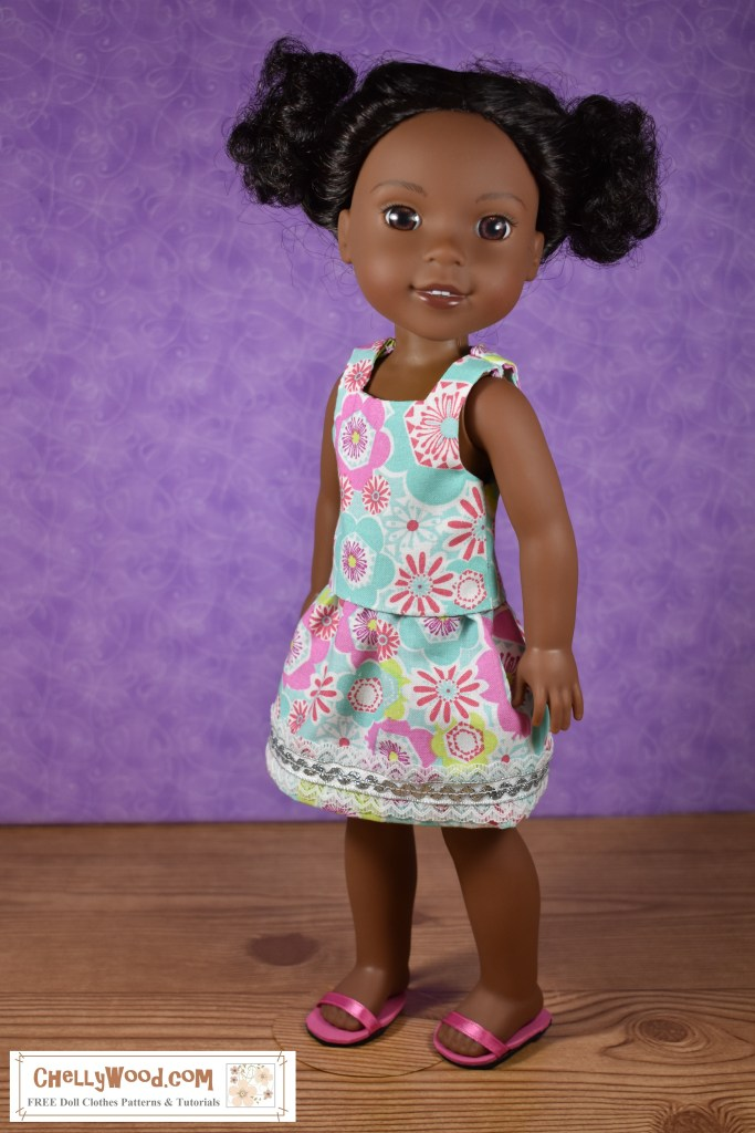 This image shows a Wellie Wisher doll modeling a handmade outfit designed by Chelly Wood (a doll clothing designer). The top is a sort of sleeveless blouse and the skirt is edged in rick rack and lace trim. You can download the free printable sewing patterns for making this outfit and watch the sewing tutorials at ChellyWood.com
