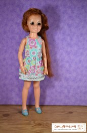 Here we see a vintage 18-inch Crissy doll wearing handmade clothes including a tank-top-style of sleeveless summer shirt and a cute elastic-waist skirt trimmed in lace, ribbon, and ricrac. The 70's pattern on her clothes' fabric is dotted with pink and bright green flowers which are reminiscent of the 1970's decor and fashions. Her Mary Jane shoes match the background turquoise color of the fabric. At the bottom of the image, the URL ChellyWood.com tells you where you can find free P.D.F. patterns and video tutorials with audio instructions for sewing this skirt-and-top clothing set for your vintage Crissy doll.