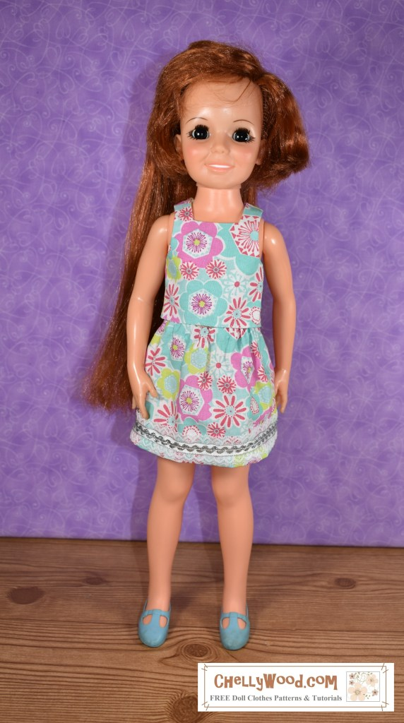 "Image shows the 18"" or 46 cm Crissy doll (a vintage doll designed and marketed by the Ideal Toy Corporation) wearing a handmade tank top shirt and matching skirt with ribbon and lace embellishment. In this photo, Crissy faces the camera. This is one of four images of the Crissy doll posted to the ChellyWood.com website, where you can find free printable sewing patterns to make this outfit. The doll poses at a slightly different angle in each of the four photos, offering a little different light and shadow on the sleeveless shirt and above-the-knee skirt. The fabric is designed with bold images of flowers in a style that's reminiscent of the early 1970's when the Crissy doll was available in stores for sale. These flowers seem to ""dance"" across the fabric in pink, green, and turquoise colors, along with bouncy stems and flashes of leaves. The skirt's ribbon is silver, and it edges the skirt's hem. Once again, to find the free printable sewing patterns for this shirt and skirt combination, go to ChellyWood.com"
