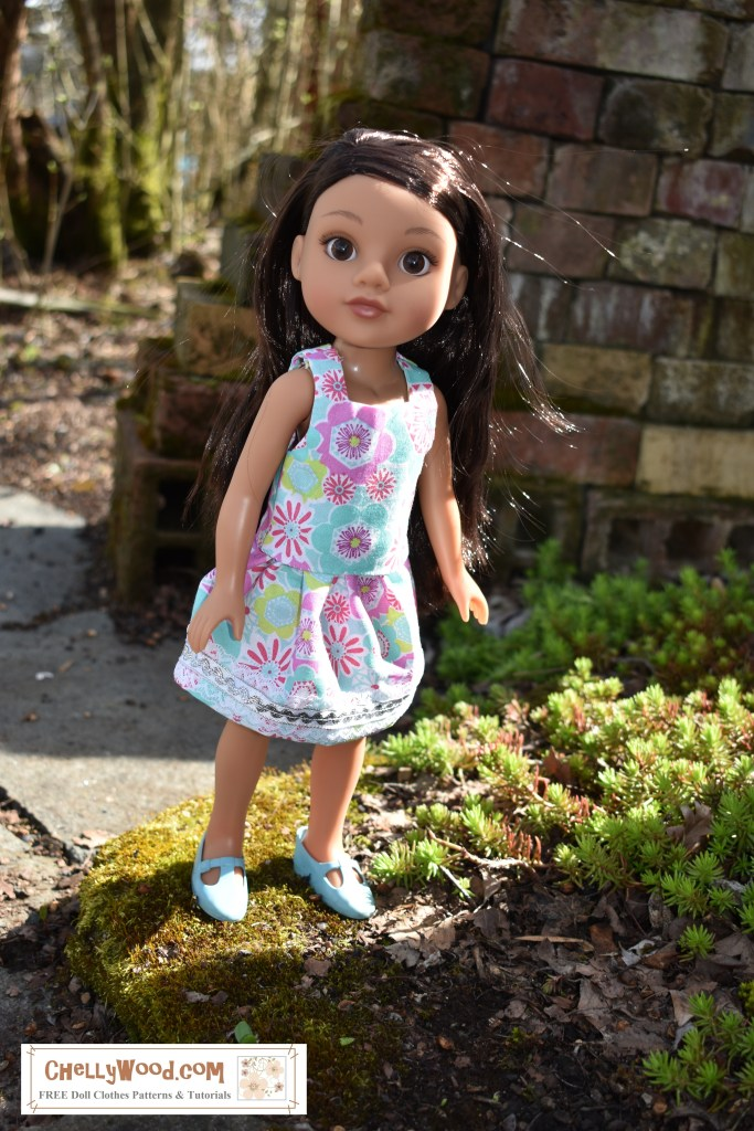 Consuelo, the Hearts for Hearts doll, seems to be striding through a magical garden in this image, sporting a handmade blousy tank top shirt and matching skirt. The fabric of this outfit is splattered with colorful flowers in a 1970's flower power theme. The bottom of her skirt is adorned with rick rack, ribbon, and lace. She looks delicate and feminine like a little fairy in the morning sunlight with tiny green plants at her feet. ChellyWood.com offers free printable sewing patterns for making these doll clothes which fit Hearts4Hearts girls as well as other similar-sized dolls.