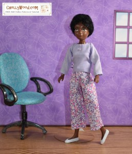 Soul, one of the 9-inch World of Love dolls from Hasbro, stands alone in a room with a single office chair and window. She wears capri pants made of a cotton fabric that's decorated with tiny pink flowers and lavender-colored vines. She wears a matching lavender shirt with two tiny buttons at the top. The shirt has long sleeves and a conservative rounded neckline but no collar. She wears tiny white plastic flats. If you would like to make an outfit like this for your 9-inch (23 cm) dolls, you can find the free, printable PDF patterns at ChellyWood.com along with tutorial videos showing how to make both the shirt and the capri pants. The website is marked with the creative commons attribution mark, so by downloading these patterns, you agree to share them on social media and tell where they came from.