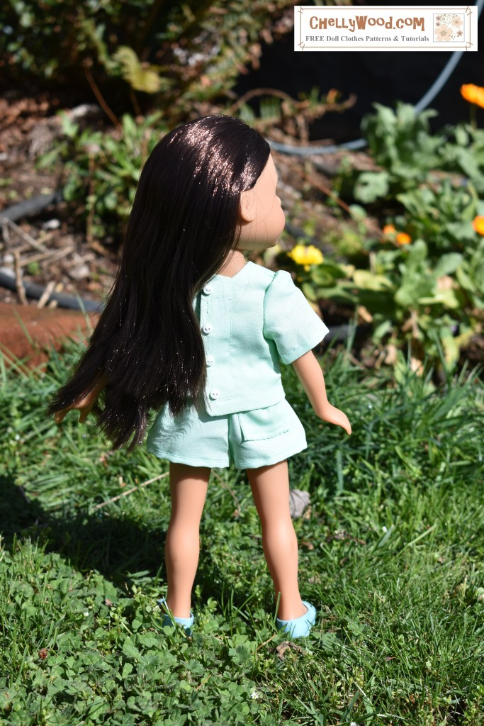A Hearts for Hearts Girls doll stands in a bright green garden with flowers in the distance. She wears mint green shorts with a single back pocket and a mint green short-sleeved shirt with buttons that adorn the back closure.