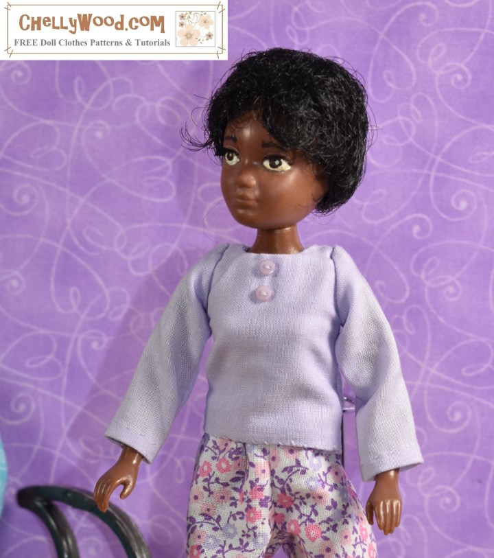 This image shows Soul, one of the dolls from the World of Love doll collection from Hasbro, wearing a hand-made shirt with two teeny-tiny lavender-colored buttons in front. This is a long-sleeve shirt made of lavender-colored cotton fabric. The free printable PDF sewing pattern for making this shirt for your 9-inch fashion dolls can be downloaded for free at ChellyWood.com