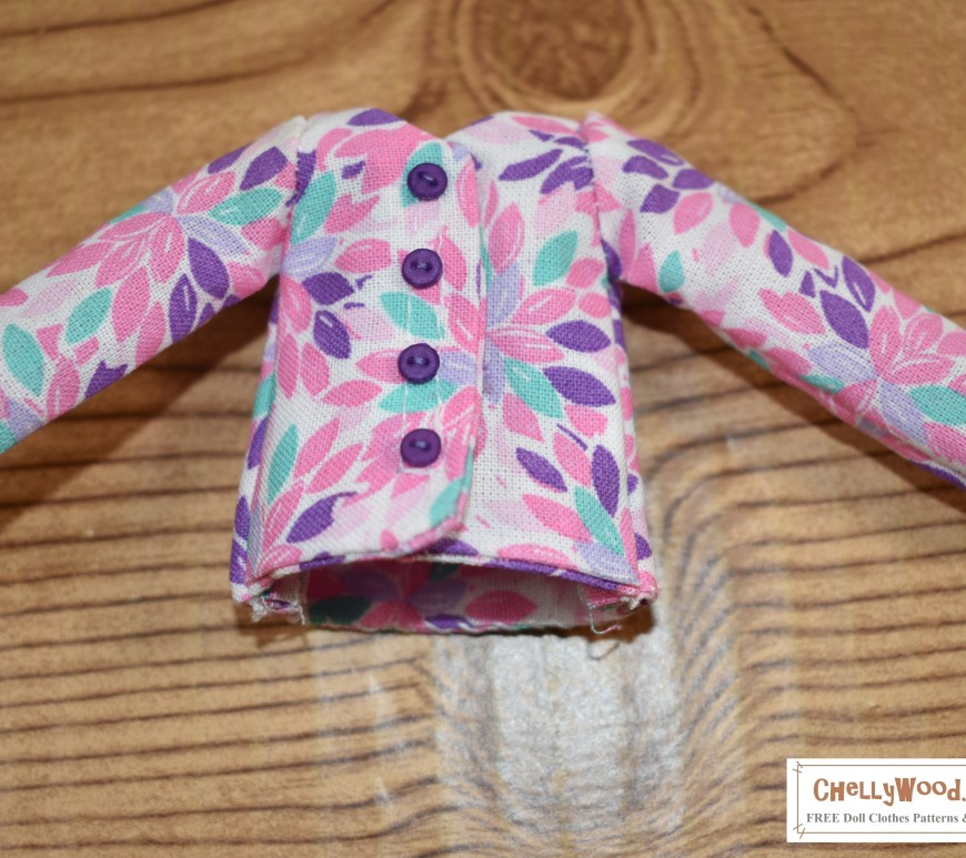 The image shows a shirt with long sleeves that has been hand sewn to fit dolls in the 9 inch or 23 cm / 24 cm size range. Free patterns for this and other 9 inch doll clothes (23 cm dolls' clothes / 24 cm doll's clothes) can be found at ChellyWood.com along with free video tutorial instructions.