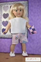 The image shows an 18 inch doll modeling a pair of pajama shorts and a pajama top. The doll holds a quilted pillow, like she's about to participate in a pillow fight. She wears slippers shaped like bunny rabbits. Behind her on the wall is a quilt with fabrics sewn in the shape of appliqued hearts. The overlay offers the URL of the website where you can download and print the PDF sewing patterns for making these flannel shorts and the super-easy-to-sew felt top: ChellyWood.com