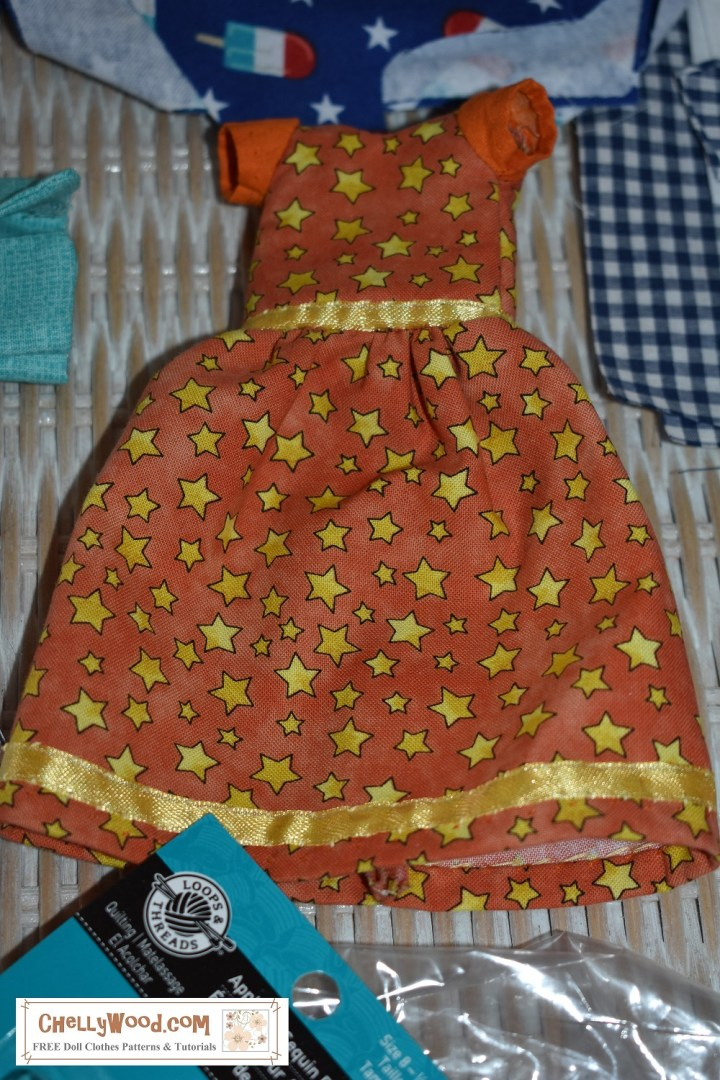 The image shows a dress made for 8-inch or 9 inch dolls. The fabric is orange, and it's decorated with tiny yellow stars. There's a yellow ribbon trim and a yellow ribbon waistband. The sleeves are solid orange. The watermark offers the URL of the website where you can find lots of free printable sewing patterns for dolls of many shapes and sizes: ChellyWood.com