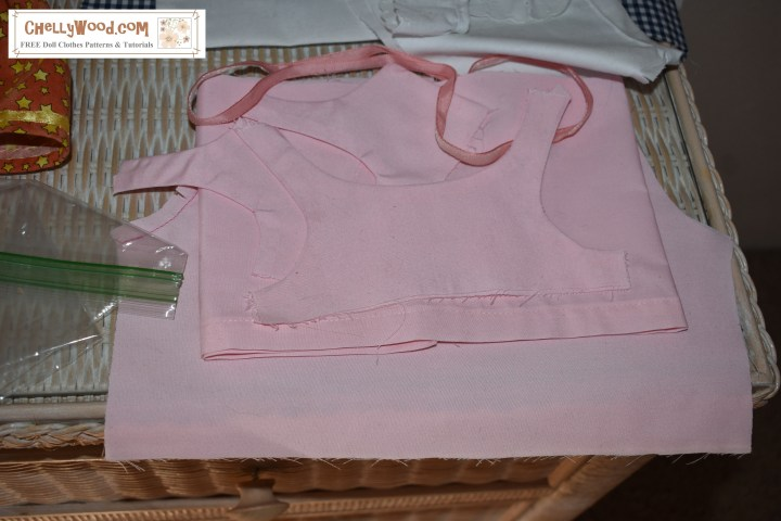 The image shows a partially sewn pinafore that was designed to fit an 18 inch doll. The fabric is solid pink. The watermark says the name of the website where you can find lots of free printable sewing patterns for dolls of many shapes and sizes: ChellyWood.com