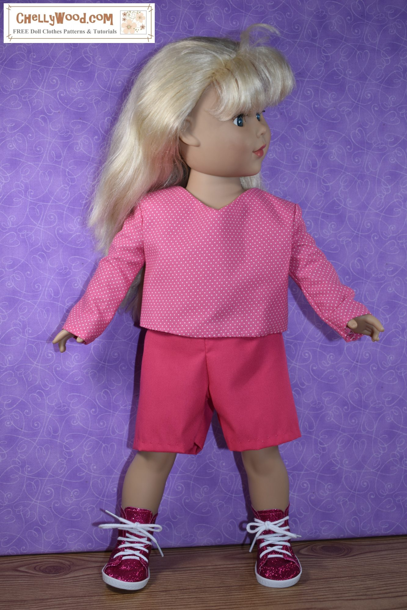 """This photo shows an 18"""" doll wearing a pair of handmade solid pink shorts with a long-sleeved pink-and-white polka dot shirt that has a slight V-neck. The watermark on this photo tells you where you can go to download the free printable PDF sewing patterns for making 18"""" doll clothes including this complete outfit of shorts and a shirt to fit dolls in the 18 inch (45 cm to 46 cm) size range; the website is ChellyWood.com"""