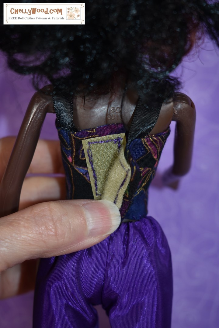 The image shows a Queens of Africa doll (found at https://queensofafricadolls.com/) modeling a strappy summer shirt in the colors black, purple, and gold. The person holding the doll is showing the viewer that when you open up the shirt at the back, it uses Velcro as a closure.