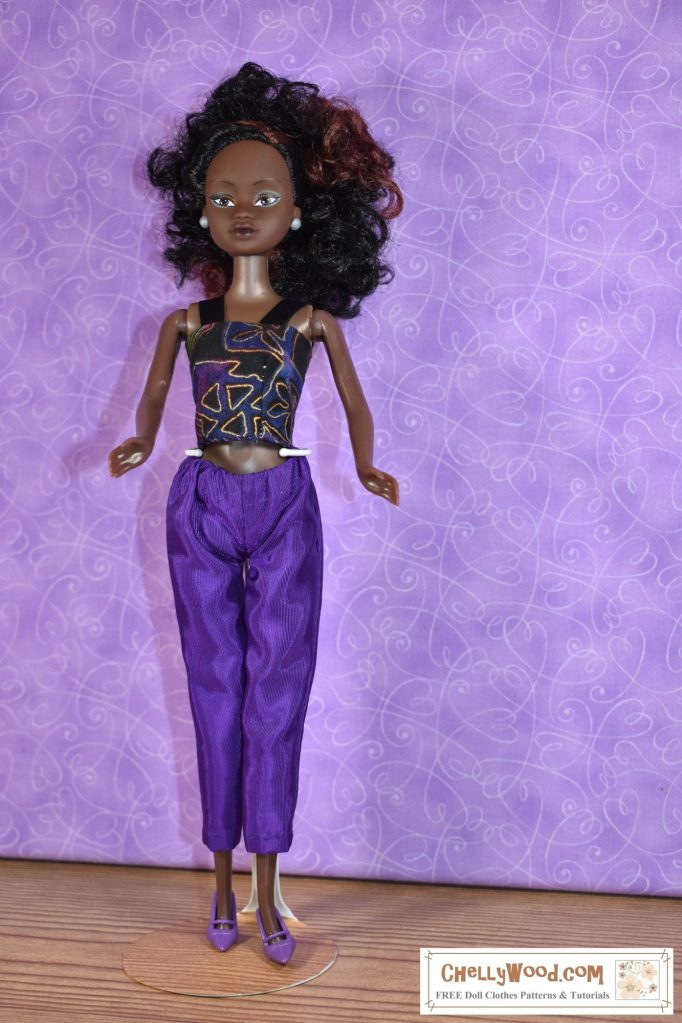 Visit ChellyWood.com for free printable sewing patterns and tutorials for sewing doll clothes to fit dolls of many shapes and sizes. The image shows a Queens of Africa 11 inch fashion doll wearing a handmade pair of ankle pants and a strappy summer top in purple, black, and gold colors. The Queens of Africa dolls can be purchased from the Slice by Cake company at https://queensofafricadolls.com/