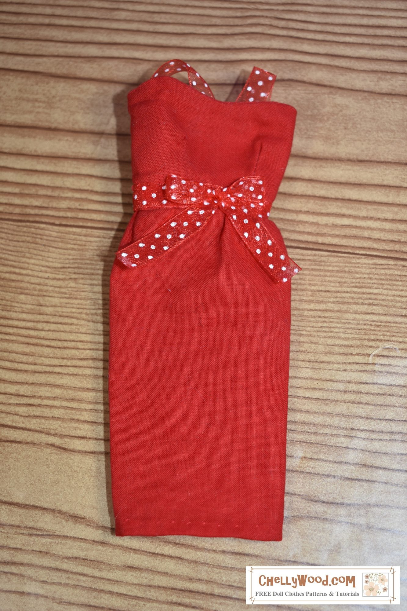The image shows a red cotton pencil-skirt dress with an opaque ribbon tied around the waist. The ribbon is also red with white polka dots. The straps on this pencil-skirt dress's bodice match the polka-dot ribbon tied around the dress's waist.