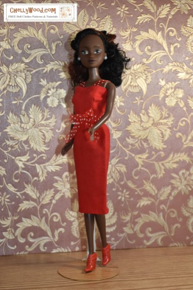 Here we see a Queens of Africa doll wearing a red cotton pencil-skirt dress with an opaque ribbon tied around the waist. The ribbon is also red with white polka dots. The straps on this pencil-skirt dress's bodice match the polka-dot ribbon tied around the dress's waist. The dress would be perfect for a date on Valentine's Day!