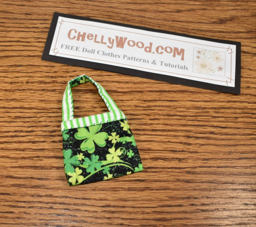 "The image shows a pretty fashion doll purse in green, white, black, and yellow. The strap of the doll's purse has green and white stripes. The body of the purse is made of black fabric decorated with green and yellow shamrocks. It's just the right size for 11"" to 12"" fashion dolls like BarbieDolls, Liv Dolls, Poppy Parkers, Skippers, Francies, Midges, and similar-sized dolls. There's a sign above the purse that says where you can find and download the free printable PDF sewing pattern for this dolls' purse: ChellyWood.com"