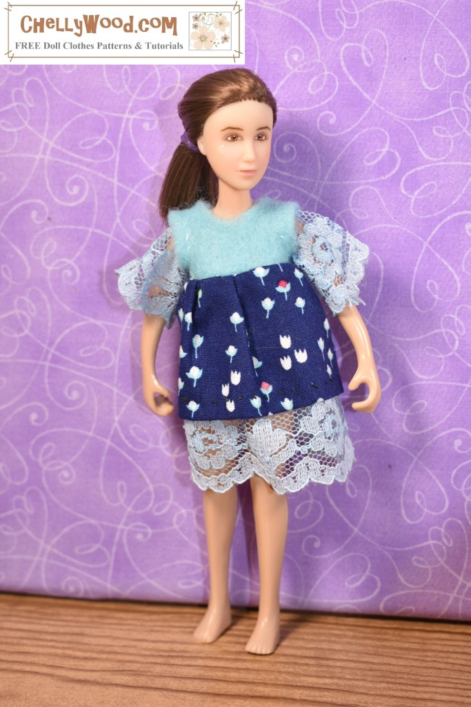"""Here we see a 6-inch (15 cm) miniature doll wearing a handmade dress made of cotton, felt, and lace. Below the image it says, """"Click here for all the free printable sewing patterns and tutorial videos you'll need to sew this dress for your 6 inch 1:12 scale doll (like Breyer Classic Rider dolls): https://wp.me/p1LmCj-GQd """" and if you click on that link, it will take you to a page where you can easily download the free printable PDF sewing pattern and watch the tutorial video for sewing a miniature dress for 6 inch dolls like the Classic Breyer Riders. These dolls come in 1:12 scale like many dolls that are designed for 1:12 scale dollhouses. The dress fits her almost like a pinafore, with the skirt being somewhat short. However, a swatch of lace at the bottom of the dress's skirt helps to lengthen the dress to the doll's tiny knees. This doll dress pattern and its accompanying tutorial video are available on ChellyWood.com"""