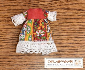 "The image shows a handmade folk-style dress that fits 4 inch, 5 inch, or 6 inch dolls (10 cm to 15 cm dolls). The dress shown uses a folksy cotton fabric for the dress's sleeves and skirt, red felt for the bodice, and the whole dress is trimmed in white lace. The watermark lets you know that if you go to ChellyWood.com, you'll find ""free doll clothes patterns and tutorials."""