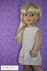 The image shows an 18 inch Madame Alexander doll (similar in body style to the American Girl dolls) wearing a sleeveless shirt and matching skirt. They're made of a confetti-print fabric in many colors on a white background. Click on the link in the caption, and it will take you to a page where you can download and print all the free printable sewing patterns for making these doll clothes, along with links to tutorial videos that show you how to make this outfit.