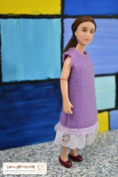 The image shows a Breyer 6 inch rider doll wearing a purple felt dress with eyelet lace trim. Please go to ChellyWood.com for the free printable PDF sewing pattern and easy-to-sew tutorial video that will show you how to make this dress (great for beginners and kids learning to sew)! Please click on the link in the caption to navigate to the right page for this pattern and tutorial.