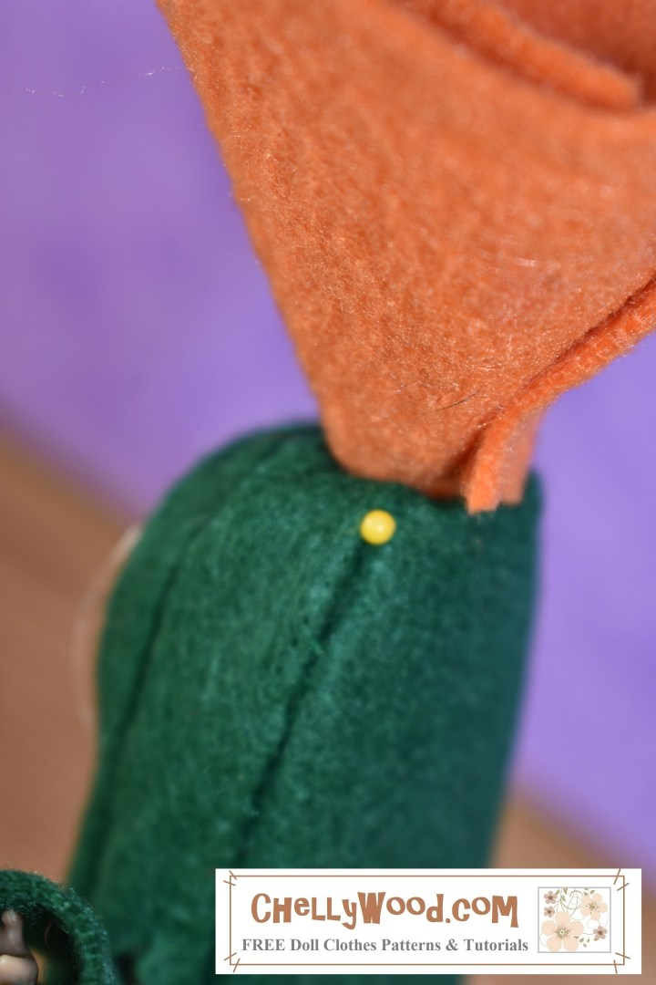 The image shows the Chelsea doll's Halloween or school play cactus costume from the back of the head. A straight pin has been inserted into the green felt of the head portion of the costume, to hold the cactus rose in place.