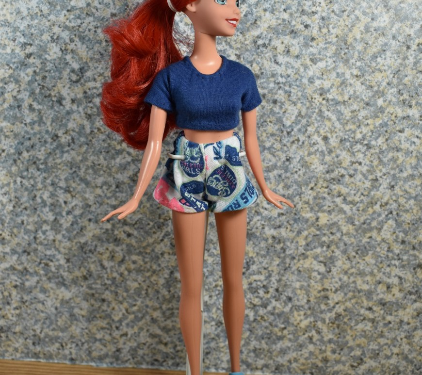 The image shows an Ariel Disney Princess 10 inch doll dressed in a crop top and shorts. Click on the link in the caption, and it will take you to a page where you can download and print all the free printable sewing patterns for making these doll clothes items, along with links to tutorial videos that show you how to make this outfit.