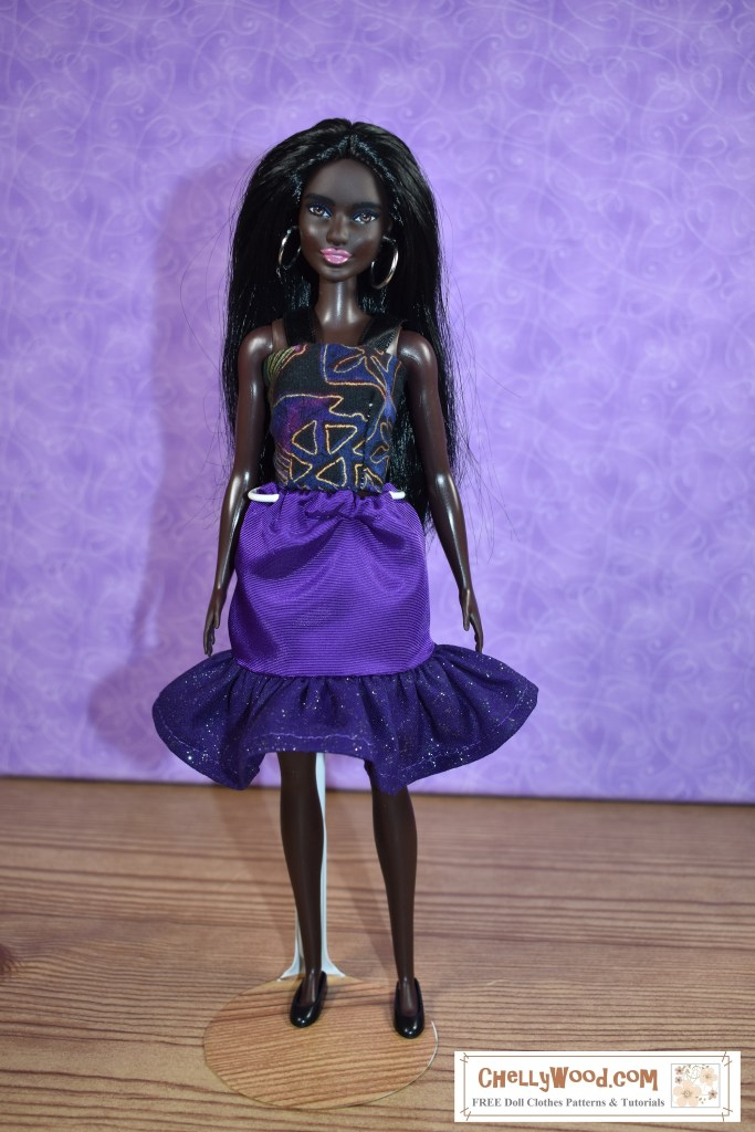 The image shows a modern Barbie doll wearing a handmade elastic-waist skirt with a glittery ruffle and a handmade tank top with gold print. Click on the link in the caption, and it will take you to a page where you can download and print all the free printable sewing patterns for making these doll clothes, along with links to tutorial videos that show you how to make this outfit.