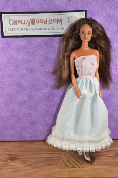 """Here we see a vintage Barbie doll with a 1980's """"Teresa"""" head that has long brown hair. The doll is wearing a strapless dress with a pink bodice, a white skirt, and at the bottom of the skirt, the ball-gown-style long dress is trimmed in square-pattered lace. This dress could be worn for a prom or as a wedding dress. Click on the link in the caption, and it will take you to a page where you can download and print all the free printable sewing patterns for making these doll clothes, along with links to tutorial videos that show you how to make this outfit."""