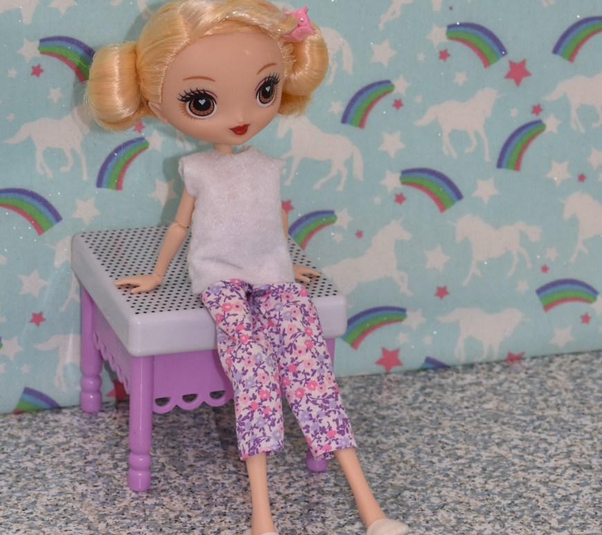 Here we see the G doll from the Kuu Kuu Harajuku television show modeling a pair of handmade pajamas. She wears a sleeveless top, a pair of elastic-waist pants, and a pair of felt slippers. She kicks up one foot playfully while leaning back on a stool in a bedroom of a dollhouse. To make this easy-to-sew pajama outfit for you G-doll or other Kuu Kuu Harajuku dolls in the 10 inch size range, please visit ChellyWood.com for free printable sewing patterns and tutorial videos teaching you how to make this and other outfits for dolls of many shapes and all different sizes.