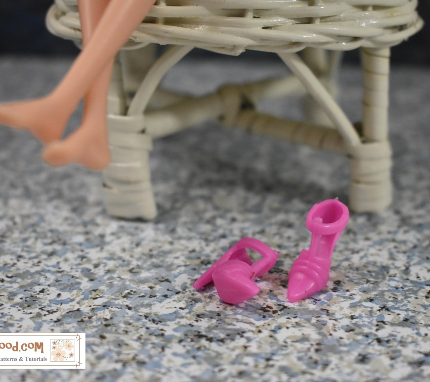 This image, showing a doll's tiny criss-crossed legs and itty-bitty feet is found at ChellyWood.com, where a blog post encourages blog followers to dialog about doll shoes in the comments. In this image, the doll appears to be seated in a wicker chair and her bare feet are a bit out of focus. In the foreground, however, her shoes are sharply focused, and they are pink with a T-strap. They may only be a centimetre long with an even tinier heel. The blog post that accompanies this image is great for anyone wanting to chat with other doll collectors and doll shoe makers about collecting and making shoes for dolls.