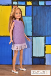 The image shows a Stacie doll wearing a purple felt dress with eyelet lace trim. Please go to ChellyWood.com for the free printable PDF sewing pattern and easy-to-sew tutorial video that will show you how to make this dress (great for beginners and kids learning to sew)! Please click on the link in the caption to navigate to the right page for this pattern and tutorial.