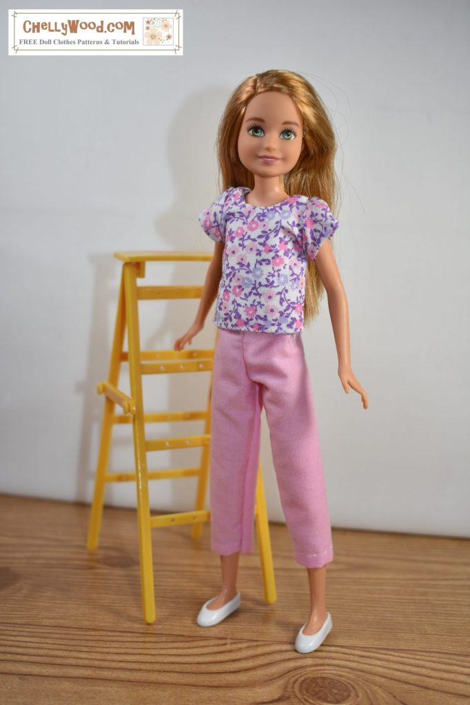 The image shows Mattels Stacie doll (Barbies little sister) wearing a pair of capri pants and a short-sleeved cotton shirt. She stands beside a ladder in front of a bare white wall, like shes about to start painting the wall. The free printable sewing patterns and tutorial instructional videos that tell you how to make this outfit for your Stacie doll can be found at the link found in the caption.