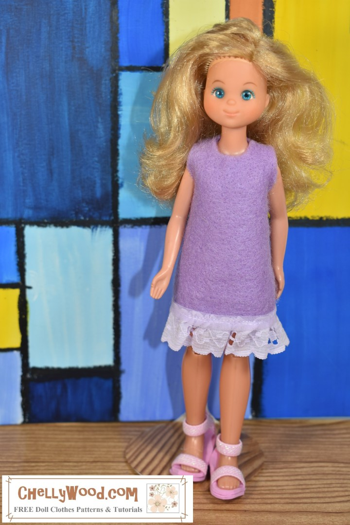 The image shows a vintage Sunshine Family female doll (the mom or mother Sunshine Family doll from the 1970's). She wears a handmade felt dress trimmed in lavender eyelet lace. To learn how to sew this easy doll clothes sewing project, and to download the free printable PDF sewing pattern for this dress (which fits a lot of different dolls including but not limited to Monster High dolls, Ever After High dolls, Stacie dolls, Kuu Kuu Harajuku dolls, and Sunshine Family dolls, please visit ChellyWood.com
