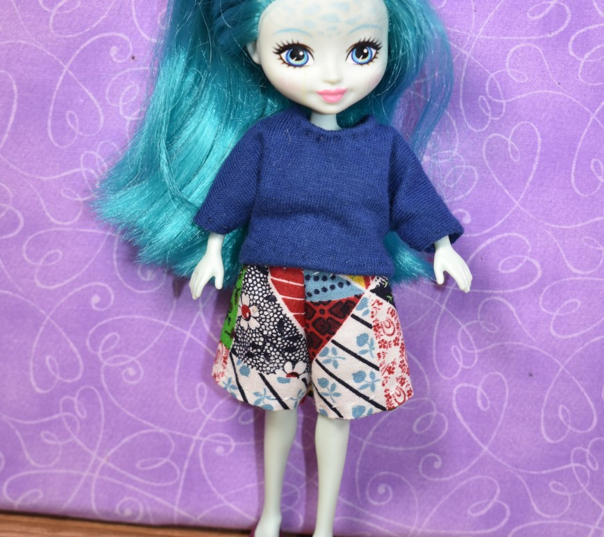 The image shows a lovely blue-haired pale-skinned doll with speckles on her forehead. She's a Taylee Turtle character doll from Mattel's Enchantimals collection, and she's wearing a handmade T-shirt and a pair of handmade shorts. If you'd like to make this outfit for your tiny miniature dolls, please click on the link in the caption. It will take you to the free doll clothes patterns and tutorial videos.