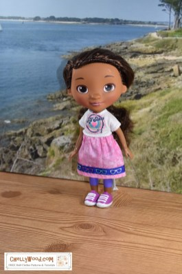 Here stands a Doc McStuffins at 21 cm or 8 and half inches tall, wearing a handmade T-shirt and easy-to-sew elastic-waist skirt. The doll is standing on a wooden platform near a beach. Would you like to make a shirt and skirt for your Doc McStuffins dolls? Click on the link in the caption, and it will take you to a page where you can download and print all the free printable sewing patterns for making these doll clothes, along with links to tutorial videos that show you how to make this outfit.
