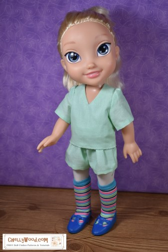 The image shows a Disney Princess Elsa 13 inch doll wearing handmade shorts, a handmade shirt, and hand-stitched stockings. If you want to make this outfit, please click on the link in the caption. It will take you to a page where you will find all the free patterns and tutorial videos you'll need to sew this outfit for your 13-inch hard plastic Disney Animator dolls.