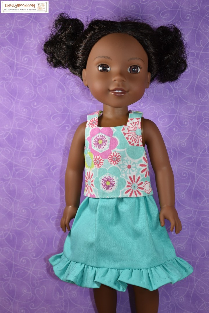 The image shows a Wellie Wisher doll in a turquoise skirt with a pretty ruffle at the bottom and a multi-colored retro-print floral tank top. Click on the link in the caption, and it will take you to a page where you can download and print all the free printable sewing patterns for making these doll clothes, along with links to tutorial videos that show you how to make this outfit.