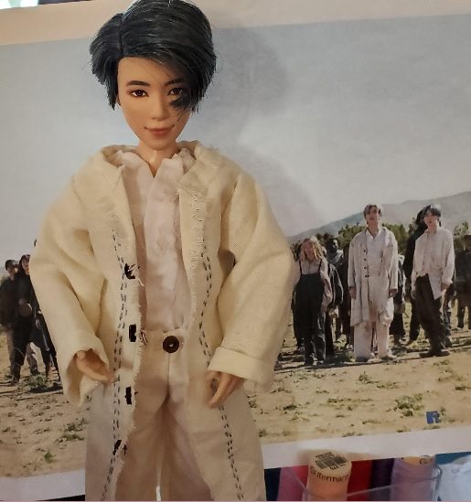 This is a photo of a BTS doll wearing handmade doll clothes including a duster with embroidered edging and tiny buttons over a gathered-collar shirt and elastic waist pants. Behind the doll is the actual BTS celebrity person dressed in the same outfit.